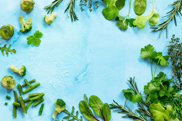 Food background. Various summer green vegetables, spices and fresh herbs on blue concrete background. Copy space, top view flat lay background.