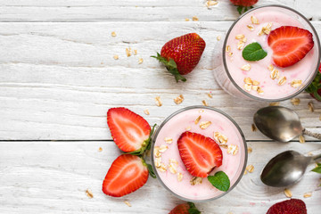healthy strawberry yogurt with oats and mint in glasses with fresh berries and spoons over white wooden table