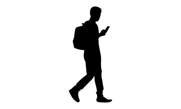 silhouette of a young man with a backpack walking while holding the phone