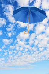 Mary Poppins Umbrella.Blue umbrella flies in sky against of white clouds.