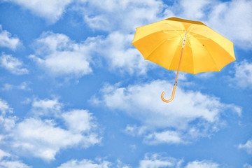 Yellow umbrella flies in sky against of white clouds.Mary Poppins Umbrella.