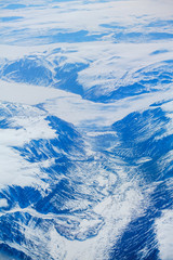 Frozen Greenland. Mountains, snow, river, glaciers. Greenland from the plane.