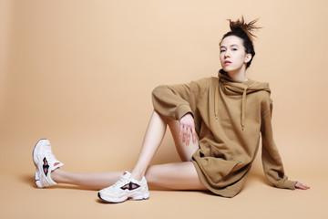 Fashion Model, Fashion, Teenage Girls. Posing over beige background Wall mural