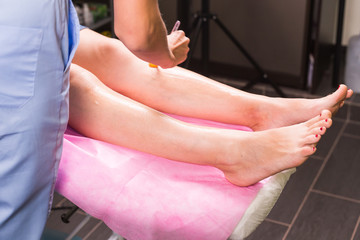 Hair removal cosmetology procedure from a therapist at cosmetic beauty spa clinic. Laser epilation. Cosmetology and SPA concept