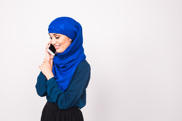 beautiful young arabian woman talking on cell phone on white background