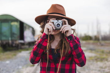 young beautiful woman wearing casual clothes and a hipster hat taking a picture with a vintage camera. Outdoors city background. Lifestyle.
