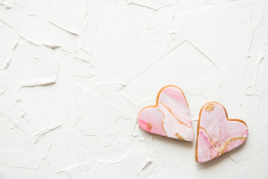 Two marble cookies in the shape of a heart on white background, top view, copy space