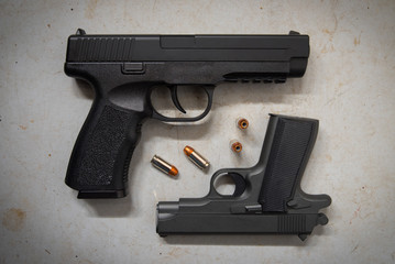 Two Handguns on Concrete Floor with Bullets