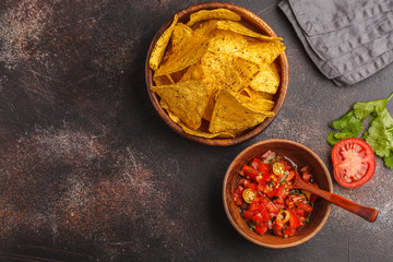 Mexican food concept. Nachos - yellow corn totopos chips with tomato sauce pico del gallo, top view, copy space.