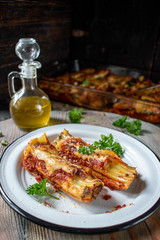 baked cannelloni pasta with spinach, ricotta, mozzarella cheese in tomato sauce on plate with parsley in rustic setting