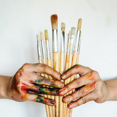 Close Up of an artist/painter hands holding paint brushes