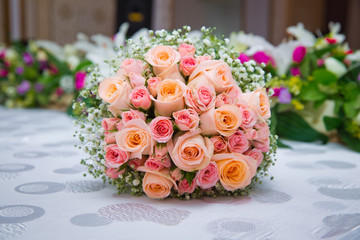Bridal bouquet with orange and pink roses of different size with handle on white background. Romantic wedding bouquet with beautiful flowers.