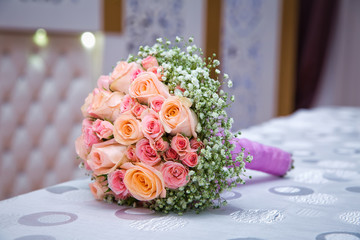 Bridal bouquet with orange and pink roses of different size with handle on white background. Romantic wedding bouquet with beautiful flowers. Elegant round bunch of fresh roses. Accessory of bride