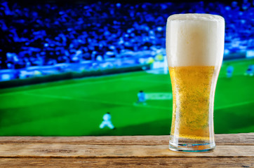 Glass of beer on a football game TV background