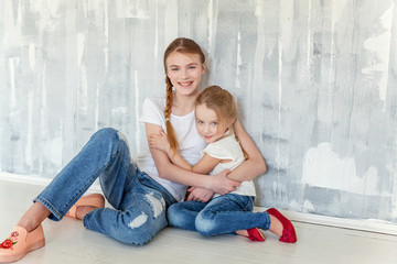 Two happy kids sitting against grey textured wall background and embracing. Adorable pretty little girl hugging tight cute teenage girl, showing her love and care. Sisters having fun at home