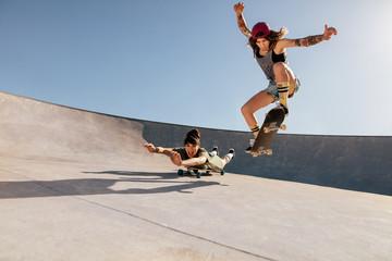Female skaters doing stunts at skate park
