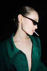 Portrait of young lady in fashionable sunglasses standing and smoking while looking aside on black background isolated