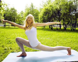 blonde real girl doing yoga in green park, lifestyle real people