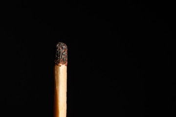Match with half-burned head on a black background closeup