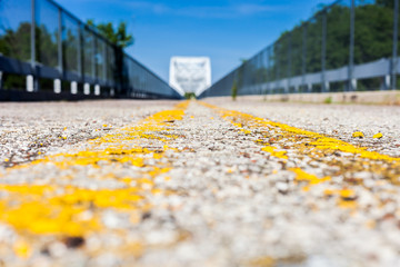 Road with double yellow centerlines shot in low angle perspective with shallow depth of field