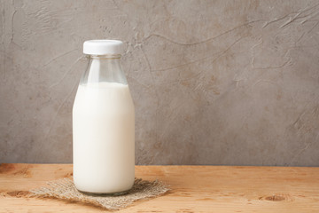 Bottle of milk on a wooden table over dark background with copy space