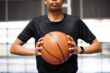 African American teenage boy holding a basketball on the court