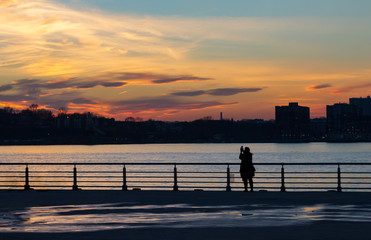 Silhouette of women photographing the sunset in New York City