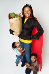 Super hero mom with her children holding groceries.
