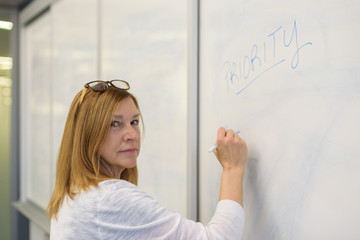 confident businesswoman writing word priority on whiteboard in meeting