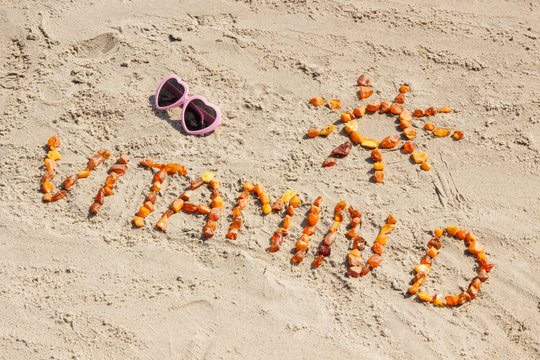 Sunglasses, inscription vitamin D and shape of sun on sand at beach, summer time and healthy lifestyle concept