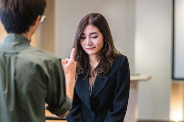 Reaw view of Furious boss scolding asian young businesswoman in formal suit by point to her face in modern office, Business mistake and punish concept