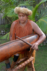 Cook Islander man plays music on a large wooden log Pate drum instrument in Rarotonga, Cook Islands