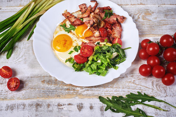 Fried eggs with bacon, tomatoes and greens. Light summer Breakfast