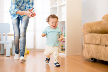 Baby toddler have a fun running in living room with his mother