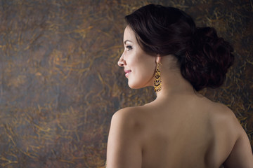 Young elegant woman in evening gold dress