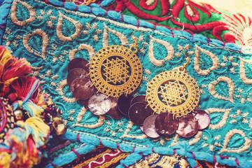 Photo sur Plexiglas Imagination golden plated earrings on blue decorative textile