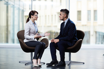 Profile view of confident dark-haired entrepreneur sitting opposite her business partner and discussing details of mutually beneficial cooperation, interior of boardroom on background