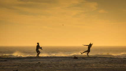 A young couple plays on the beach at sunset and the girl's hair flies as she jumps to hit a ball