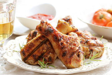 Grilled chicken legs with rosemary on table