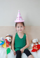 Little Asian child girl with happy birthday hat sitting on the bed.