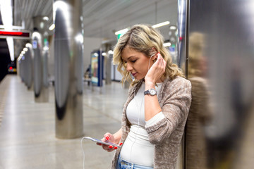 Young woman with suitcase looking at phone while waiting train in metro station.
