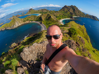 Caucasian man makes selfie at Padar Island in Flores, Indonesia.