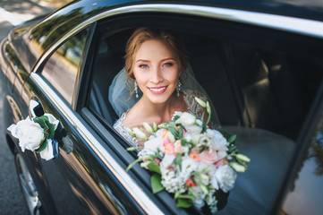 Portrait of a cute bride in a lace dress in a car window. Beautiful and smiling bride.