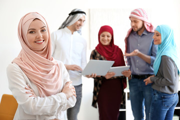 Muslim businesswoman and her colleagues at workplace