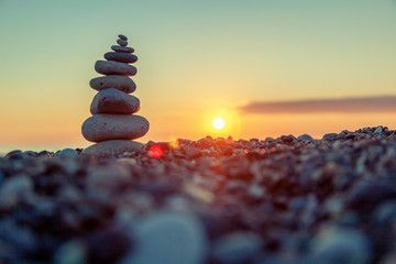 Pyramid of stones on the beach at sunset, beautiful seascape, rest and seaside vacation concept