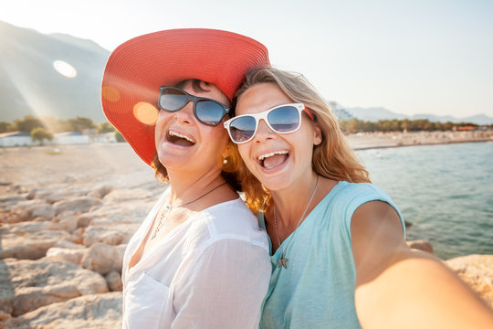 An attractive middle-aged woman with her adult daughter doing selfie on the beach, vacation and travel, cruise and sea