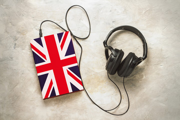 Headphones and book. The book has a cover in the form of a flag of Great Britain. Concept audiobooks. Learning languages. English