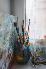 A variety of artist brushes and pencils are on the windowsill in a beautiful glass made of colored glasses. Nearby there is a picture out of focus and a colored glass vase. Vertical photo.