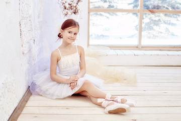 Little prima ballet. Young ballerina girl is preparing for a ballet performance. Girl in a white ball gown and Pointe near the window, beautiful red hair. Young theater actress