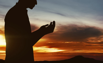 Silhouette of muslim man praying
